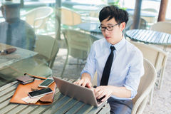 Young Asian businessman working on computer while standing in ou Royalty Free Stock Photography