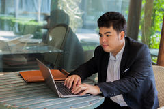 Young Asian businessman working on his laptop in outdoor scene Royalty Free Stock Image