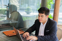 Young Asian businessman working on his laptop in outdoor scene Royalty Free Stock Images