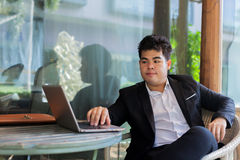 Young Asian businessman working on his laptop in outdoor scene Royalty Free Stock Photography