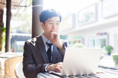 Young Asian businessman working with his laptop in outdoor scene Royalty Free Stock Photos