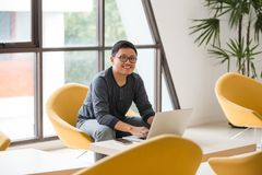 Young Asian businessman working on laptop in modern office. stock photo