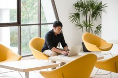 Young Asian businessman working on laptop in modern office. royalty free stock photos