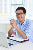 Young asian businessman working in the office. Young asian businessman looking at camera smile  in the office Stock Photography