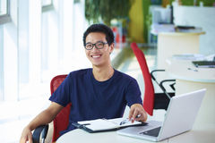 Young asian businessman working in the office. Sitting in the chair smile at camera Stock Photography