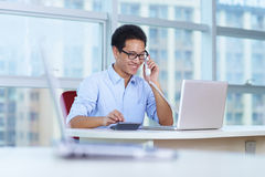 Young asian businessman working in the office. Talking on the phone Stock Images
