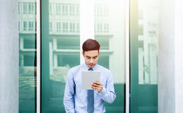 Young Asian Businessman working on tablet, Front view, Lifestyle Royalty Free Stock Image