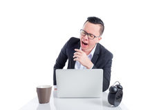 Young asian businessman  yawning while working Royalty Free Stock Photo