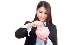 Young Asian businesswoman with a coin and piggy bank Stock Photo
