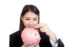 Young Asian businesswoman with a coin and piggy bank Stock Photography