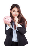 Young Asian businesswoman with a coin and piggy bank Royalty Free Stock Photography