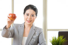 Young asian businesswoman eating healthy snack, apple Royalty Free Stock Photo
