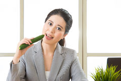 Young asian businesswoman eating healthy snack, cucumber Royalty Free Stock Photo