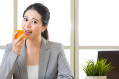 Young asian businesswoman eating healthy snack, orange Stock Photo