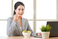 Young asian businesswoman enjoying a healthy salad Royalty Free Stock Image