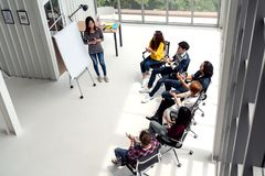 Young asian businesswoman explain idea to group of creative diverse team at modern office. stock image