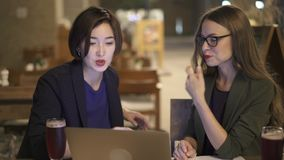 Two women with laptop talking in cafe at night