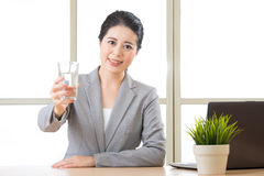 Young asian businesswoman holding glass of water Royalty Free Stock Image