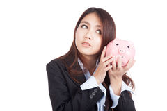 Young Asian businesswoman listen to piggy bank Royalty Free Stock Photo
