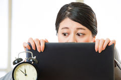 Young asian businesswoman looking at alarm clock Royalty Free Stock Photography