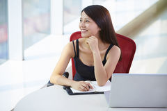 Young asian businesswoman in the office. Asian Business woman looking out of window smile  in the office Royalty Free Stock Photo
