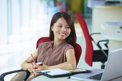 Young asian businesswoman in the office. Young asian woman looking  at laptop in the office smile Royalty Free Stock Images
