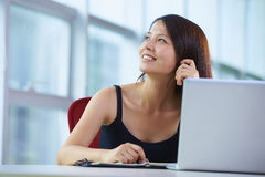 Young asian businesswoman in the office. Young asian woman looking out of the window in the office smile Royalty Free Stock Image