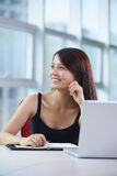 Young asian businesswoman in the office. Young asian woman looking out of the window in the office smile Royalty Free Stock Photo