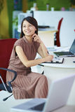 Young asian businesswoman in the office. Young asian women looking out of the window in the office smile Royalty Free Stock Photo