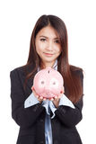 Young Asian businesswoman with piggy bank Stock Photography