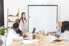 Young asian businesswoman pointing at projection screen while making presentation. In office Royalty Free Stock Photo