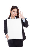 Young Asian businesswoman show OK with vertical blank sign Royalty Free Stock Images
