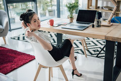 Young asian businesswoman sitting at table with laptop and looking away. Attractive young asian businesswoman sitting at table with laptop and looking away Royalty Free Stock Photo