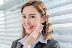 Woman use oil blotting paper. Young asian businesswoman smile and use oil blotting paper on her face stock image