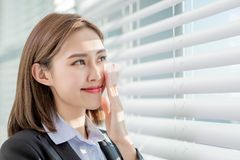 Woman use oil blotting paper. Young asian businesswoman smile and use oil blotting paper on her face royalty free stock photography