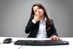 Young asian businesswoman speaking on the phone while typing Stock Images