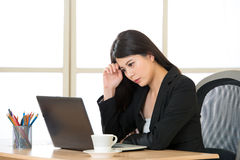 Young Asian businesswoman thinking with headache in the office. Young Asian businesswoman thinking with headache at desk in the office Stock Images