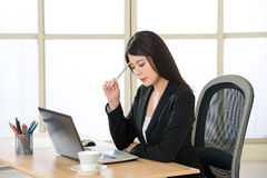 Young Asian businesswoman thinking in the office. Young Asian businesswoman thinking at desk Royalty Free Stock Photo