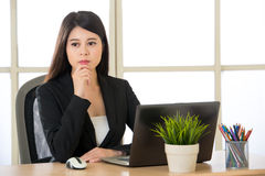Young Asian businesswoman thinking in the office. Young Asian businesswoman thinking at desk in the office Stock Photos