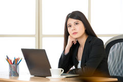 Young Asian businesswoman thinking in the office. Young Asian businesswoman thinking at desk Stock Images