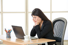 Young Asian businesswoman thinking and Staring at Computer Scree Stock Photography
