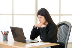 Young Asian businesswoman thinking and Staring at Computer Scree Stock Images