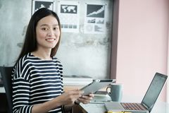 Young asian businesswoman using tablet with smiling face, positive emotion, at office, casual office life concept stock photo