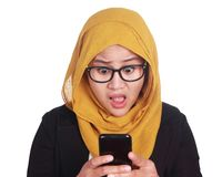 Young Asian businesswoman wearing suit shocked expression, looking at her phone. Isolated on white. Close up body portait royalty free stock images