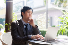 Young Asian casual businessman thinking while working in outdoor scene Stock Image