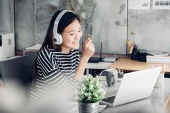Young asian casual businesswoman arm on desk rest pose with lapt. Op computer and listening music via headphone and think about work ,work at home with relax Stock Images