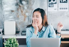 Young asian casual businesswoman yawn in front of laptop compute stock images