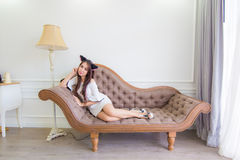 Young asian cat woman is lying on a couch in modern room Royalty Free Stock Image