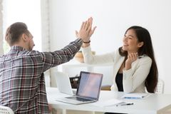 Young asian and caucasian partners giving high-five celebrating. Young asian and caucasian partners giving high five at workplace, diverse motivated colleagues Royalty Free Stock Images