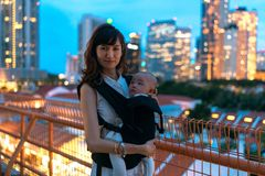 Young asian chinese mother traveling the city alone with baby in tow.  royalty free stock photo